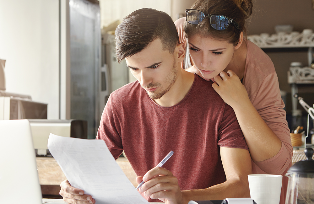 Couple looking stressed while reviewing retirement plan documents